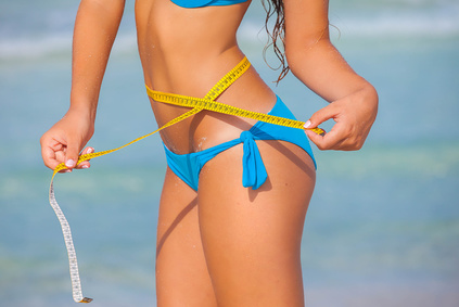 slim woman in bikini with tape measure for summer diet concept.