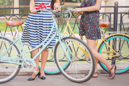 Beautiful young women dressed in summer dress travel by city vintage bicycle at heat summer time at park. They are standing at old bridge at France, Paris
